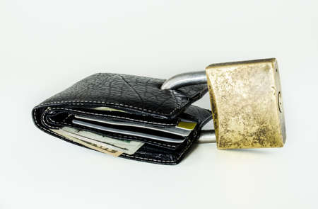 Black leather wallet with dollar bills and credit cards closed with a large padlock photo