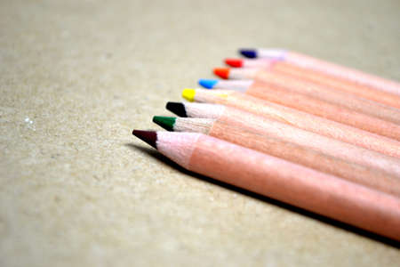 wooden pencil crayons isolated on light brown cardboard Stock Photo