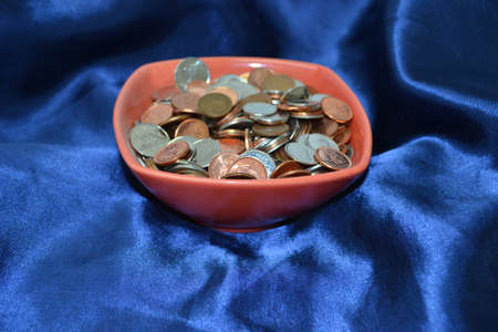 bowl of coins isolated on blue satin background