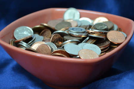 bowl of coins isolated on blue satin background close up