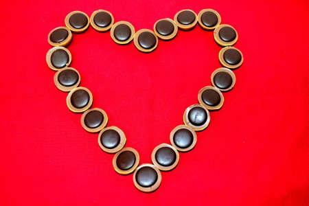 chocolates en forma de un coraz�n sobre fondo rojo