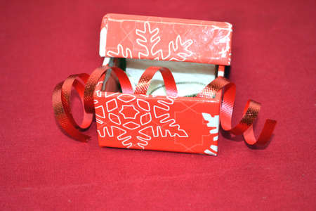 rojo caja de regalo de la Navidad con la cinta roja aislada sobre fondo rojo