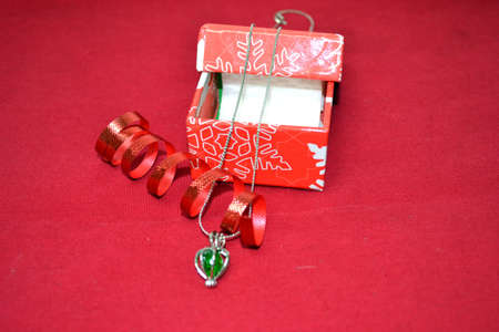jewellery with red celebratory ribbon and christmas gift box isolated on red background