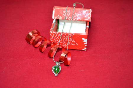 joyas con cinta roja festiva y caja de regalo de la Navidad aislado en fondo rojo Foto de archivo