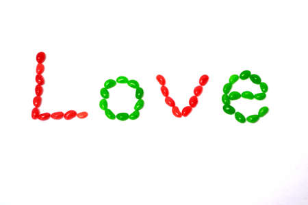 word love written with red and green jelly beans isolated on white