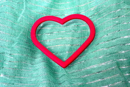 red heart cookie cutter isolated on green scarf Stock Photo
