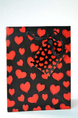 coraz�n rojo y bolsa de regalo negro aislado sobre fondo blanco de cerca