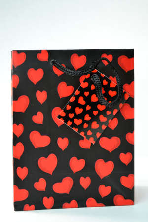 red heart and black gift bag isolated on white background close up
