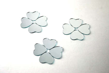 heart shaped glass mirrors in the shape of four leaf clover isolated on white