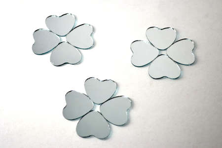 heart shaped glass mirrors in the shape of four leaf clover isolated on white close up Stock Photo