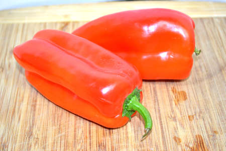 two red bell peppers on wood cutting board close up Stock Photo - 12105650
