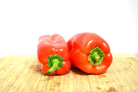 two red bell peppers on wood cutting board isolated on white background