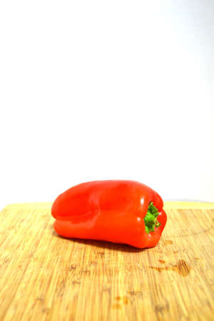 red bell pepper on wood cutting board isolated on white background