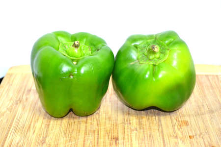 two green peppers on wood cutting board close up Stock Photo