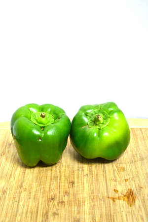 two green peppers on wood cutting board