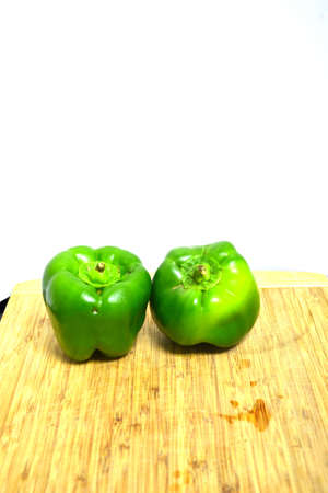 two green peppers on wood cutting board isolated on white background Stock Photo