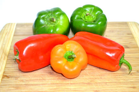 red green and orange peppers on wood cutting board close up