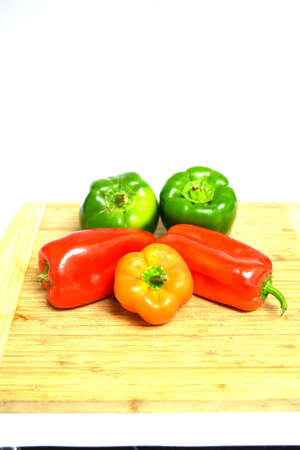 red orange and green peppers on wood cutting board isolated on white background Stock Photo - 12105678