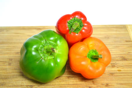 red orange and green peppers on wood cutting board isolated on white background close up Stock Photo