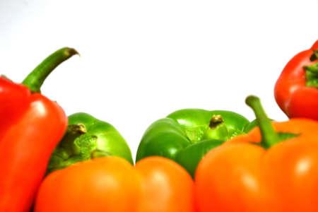 , rojo, naranja y pimientos verdes aisladas sobre fondo blanco de cerca Foto de archivo