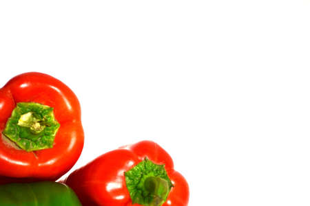 red peppers resting on top of green pepper isolated on white background Stock Photo