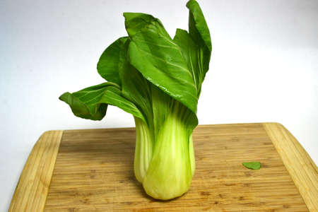 bok choy on wood cutting board isolated on white background close up