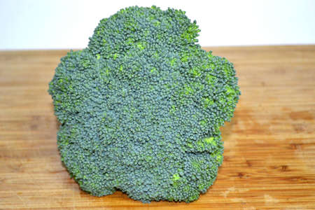 broccoli crown on wood cutting board close up Stock Photo