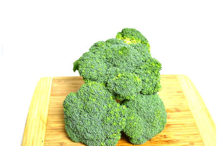broccoli crowns on wood cutting board isolated on white background close up