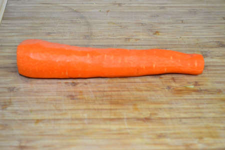peeled carrot isolated on wood cutting board