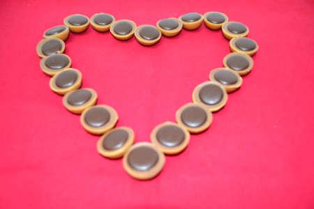 la formaci�n de chocolates en forma de coraz�n sobre fondo rojo Foto de archivo