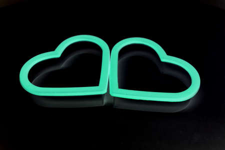 two glow in the dark hearts isolated on black background