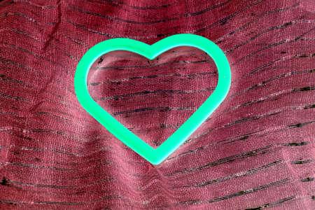 brillan en el oscuro coraz�n aislado en tela de color burdeos