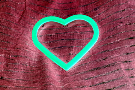 glow in the dark heart isolated on burgundy fabric Stock Photo
