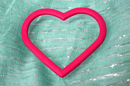 red heart on green scarf close up Stock Photo