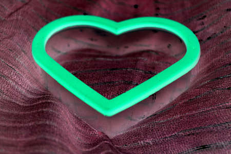 glow in the dark heart on burgundy scarf close up