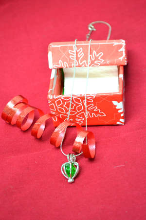 jewellery with gift box and celebratory ribbon isolated on red background close up
