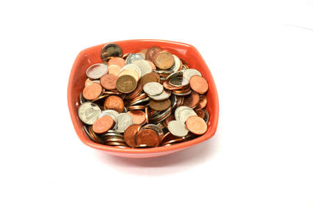 red bowl of coins isolated on white background close up