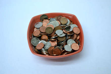 red bowl of coins isolated on pale blue background close up Stock Photo