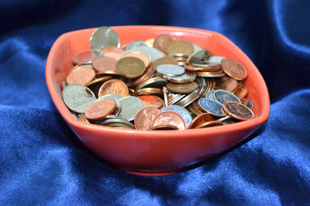 red bowl of coins on smooth blue satin close up Stock Photo