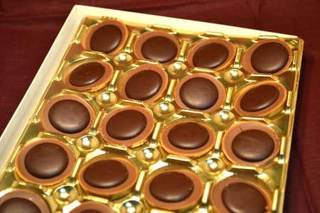 box of chocolates isolated on burgundy close up
