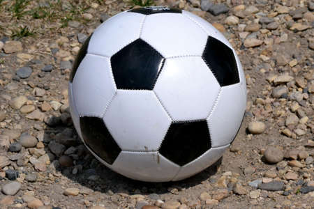 Soccer ball isolated on gravel Stock Photo