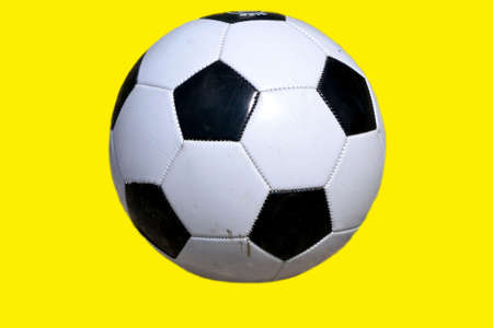 Soccer ball isolated on yellow background Stock Photo