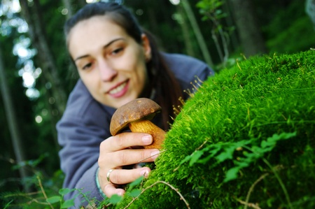 Young woman pick up the mushroom Stock Photo - 8761889