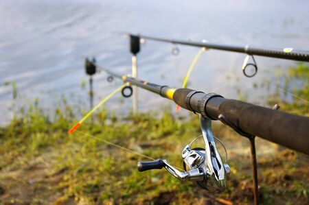 Two fishing rods on the coast of lake Stock Photo