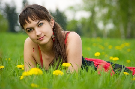 Gipsy girl on the meadow with dandelion flowers photo
