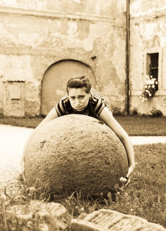 heavy lifting: Young woman try to raise big stone ball