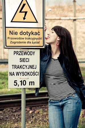 Attractive young woman licks danger sign photo