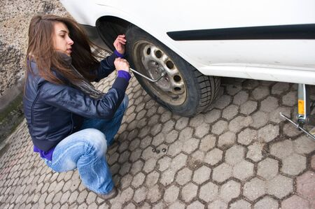 jack tar: Young woman during the wheel changing Stock Photo