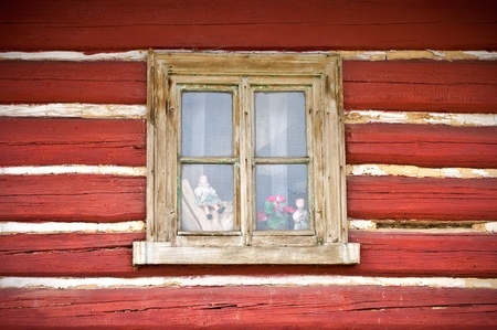 Old wooden window in the wall of cottage with few dolls inside photo