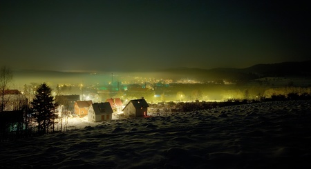 Night winter view on the small town with mist photo
